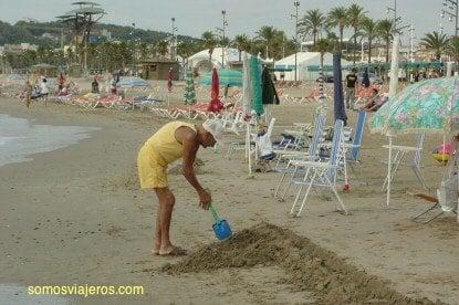 abuelo haciendo un foso en la playa