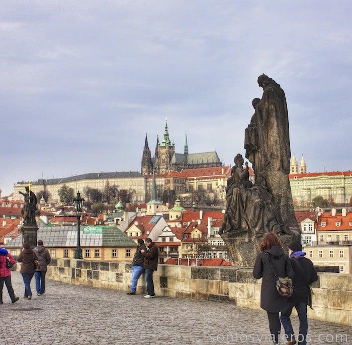 Estatuas en el puente de Carlos con el castillo al fondo