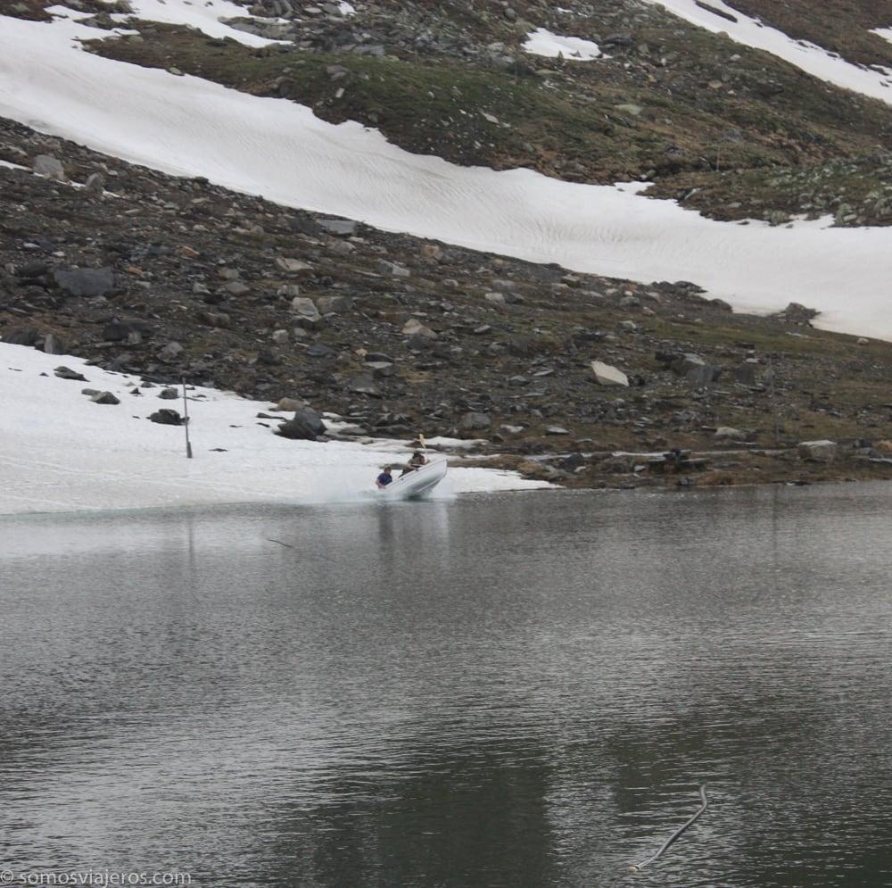 gente en un bote deslizándose en la nieve para entrar en el agua en Austria